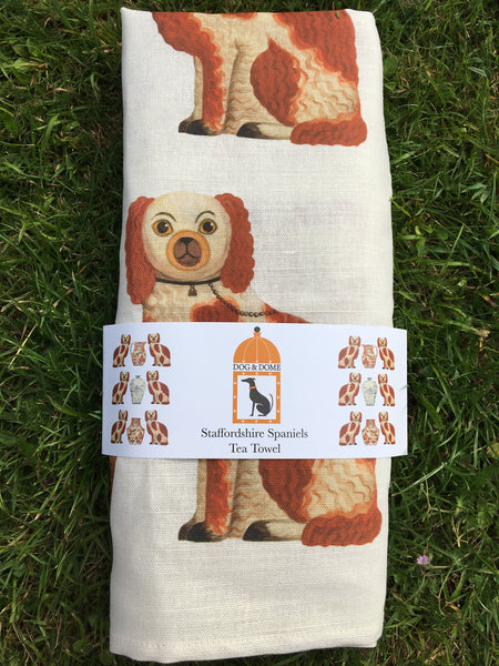 A linen/cotton blend tea towel depicting six Staffordshire Spaniels with a jug and two vases with wrap around packaging