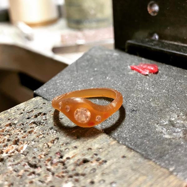 Finalizing the shape of the ring in wax and placing the stones