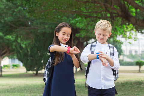 Kids playing with their dokipal smartwatches in a park