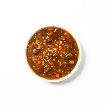 Beef barley soup, in a white bowl, on a white background