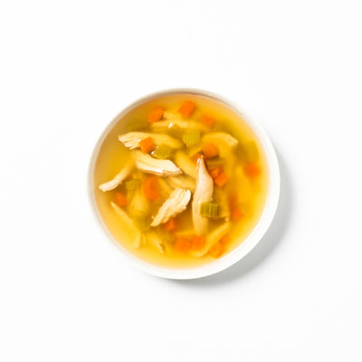 A white bowl of brothy chicken and vegetable soup