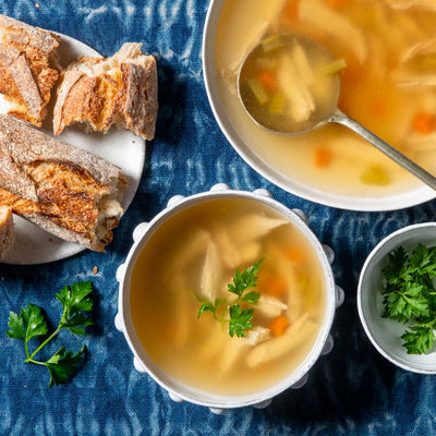 A table setting of chicken and vegetable soup, with crusty bread and parsley