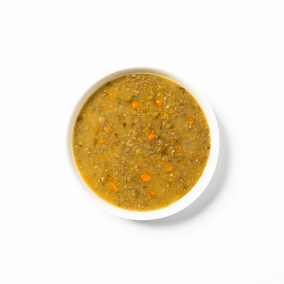 Green lentil soup made with Puy lentils in a white bowl.