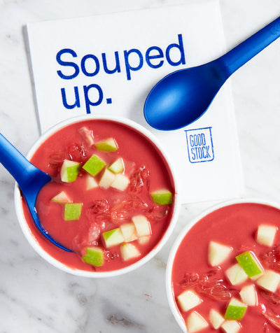 two cups of pink soup topped with dice apple, two blue spoons, and a napkin