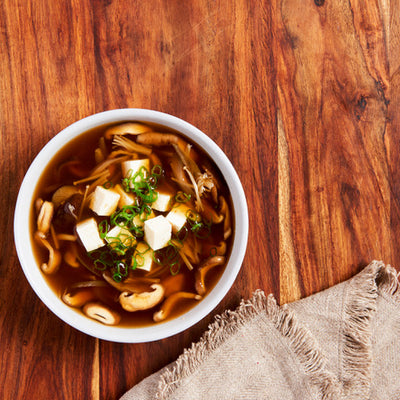A brown miso broth soup with mushrooms and tofu and sliced scallions on a wooden table