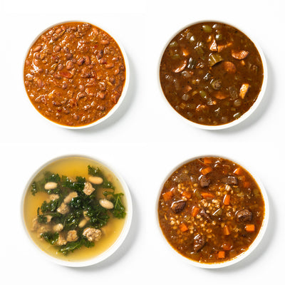 Four while bowls of soup in a grid; Beef Chili, Fried Chicken & Andouille Gumbo, White Bean Kale & Sausage Soup, Beef Barley Soup