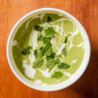 A bowl of green Chilled Cucumber soup topped with torn mint and creme fraiche