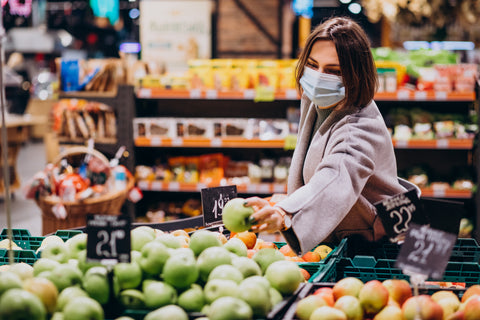 women grabbing a green apple wearing a mask in the grocery store