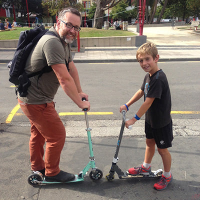Micro Dad and son scooting together