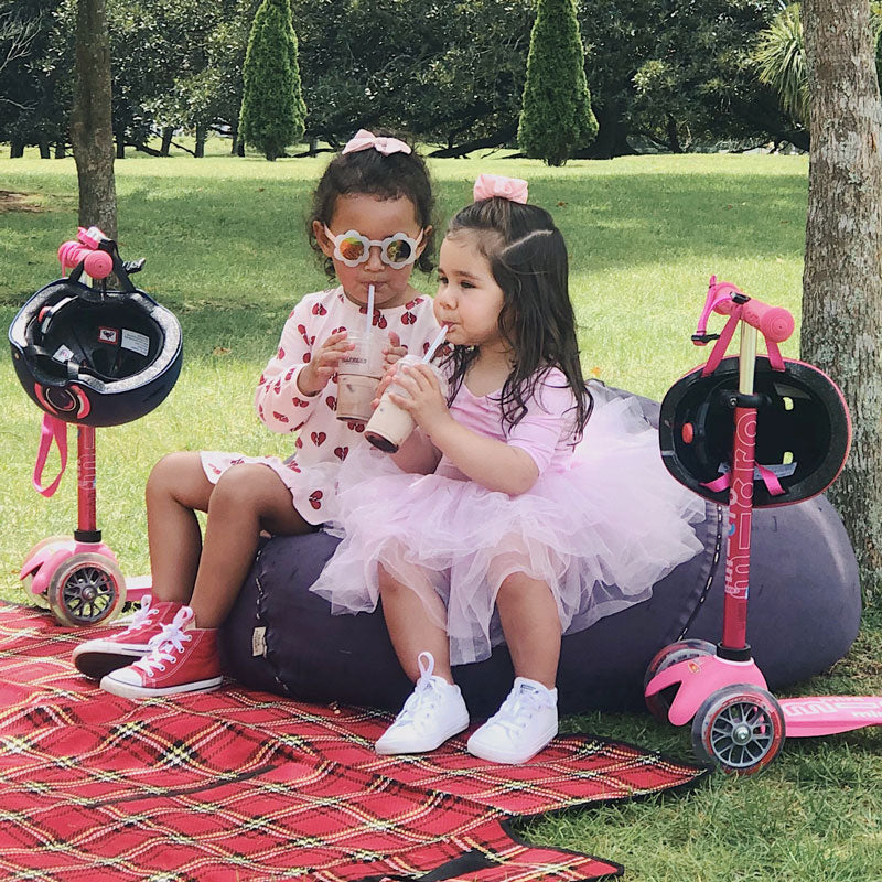 Two toddlers having picnic with Mini Micro Deluxe Pink