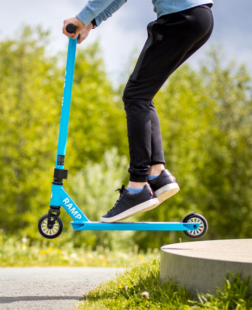 boy on his micro beginner stunt scooter ramp cyan
