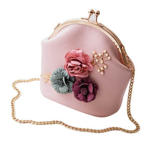 This ultra-feminine faux leather tote bag can be worn as a crossbody or a traditional shoulder purse. It features cute flower embellishments and a clutch closure.