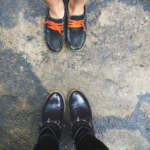two people's feet wearing second-hand shoes