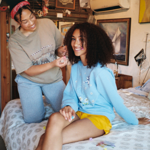 A girl braiding the hair of her friend on a bed