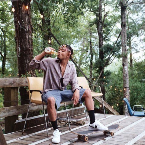 A man drinking a beer on a park bench