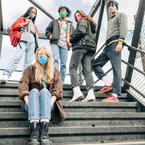 A group of people wearing Goodfair and Bumble free covid-19 face masks on cement stairs