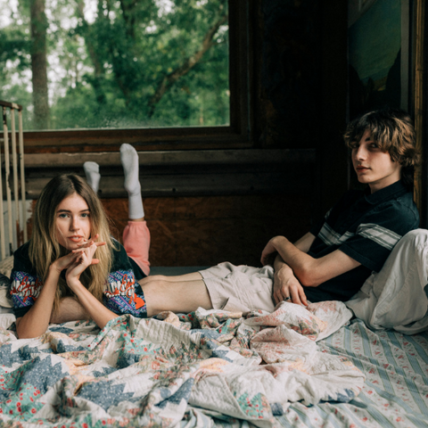A couple sitting on a bed