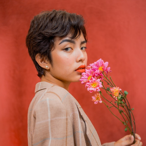 Woman with a pixie cut holding flowers and wearing a vintage blazer