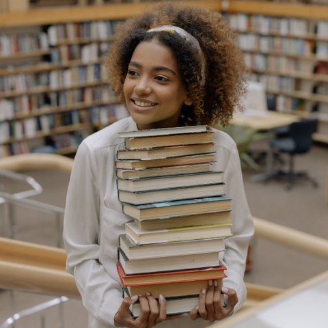 A woman with natural hair holding a stack of books in a library