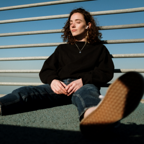 A woman sitting on the ground wearing mom jeans