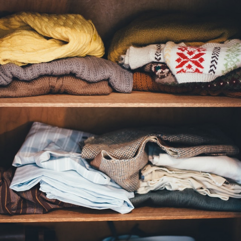 Messy sweaters on a shelf