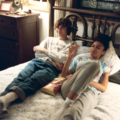 A girl and a boy lying on a bed together talking