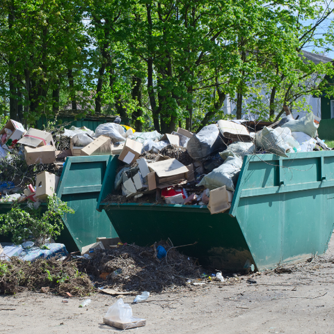 Two large trash containers filled with municipal solid waste
