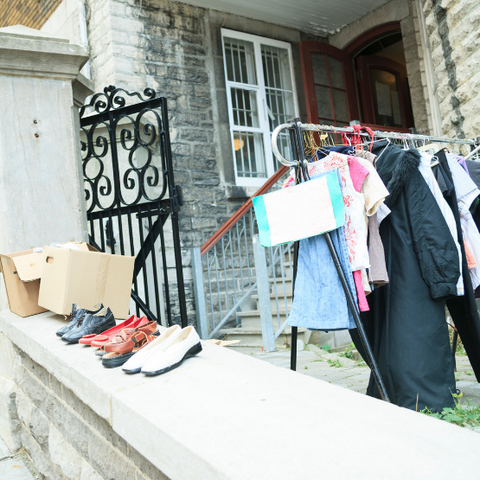 a rack of used clothing and shoes outside on the street