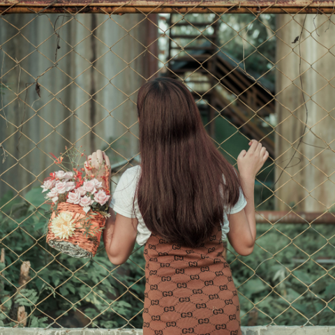 Image of a girl holding fake flowers looking through a chain link fence