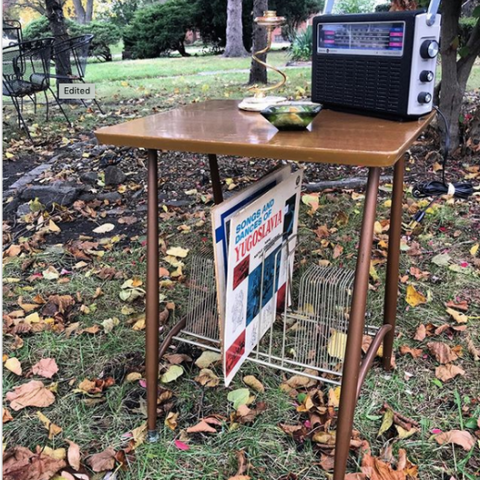 Thrifted wood record holder table with a vintage radio in an outdoor landscape