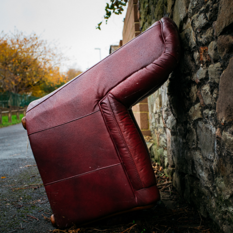 leather used chair tipped up against a brick wall in an outdoor landscape