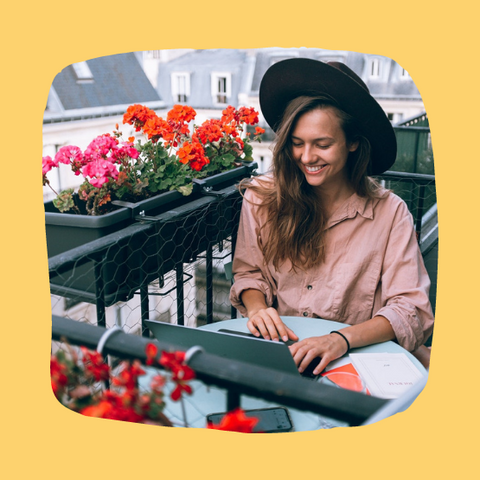 Woman smiling and wearing a hat and button up shirt working on laptop on balcony