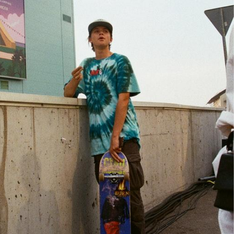 A boy with a skateboard wearing a spiral tie dye shirt