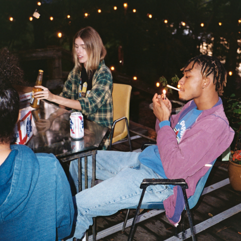 a group of young people sitting at a table drinking and smoking wearing flannel shirts t-shirts and hoodies