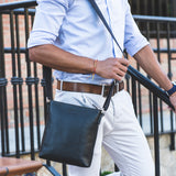 Model carrying Lucca Mens Leather Shoulder Bag from Rydal in 'Black'.