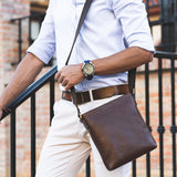 Model carrying Lucca Mens Leather Shoulder Bag from Rydal in 'Dark Brown'.