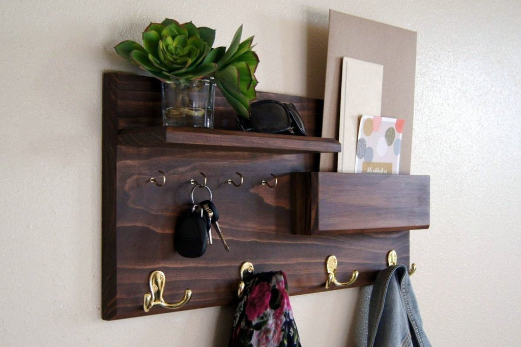 Walnut finished solid wood wall coat rack with brass coat and key hooks.