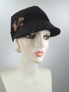 Black fabric newsboy cap with yellow and russet pattern and vintage button collage embellishment