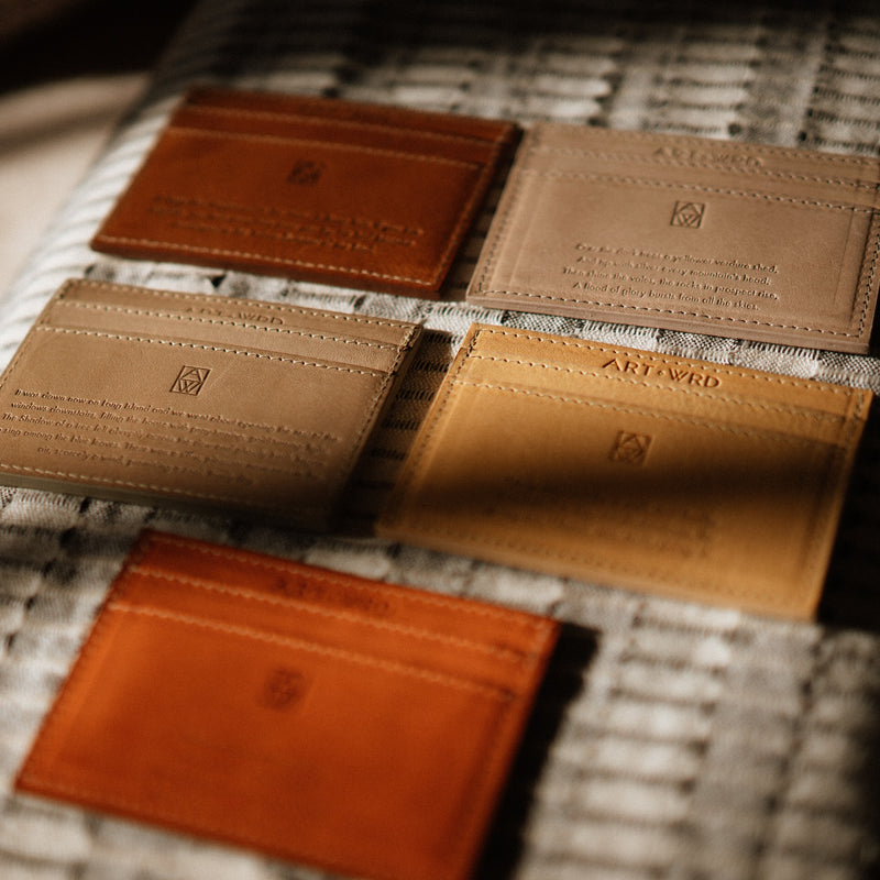 Multiple colour leather credit card holders showing embossed literary quotes