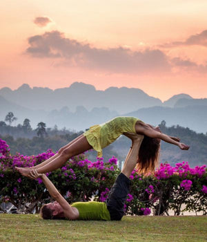 Yoga teacher practicing acroyoga with student outdoors