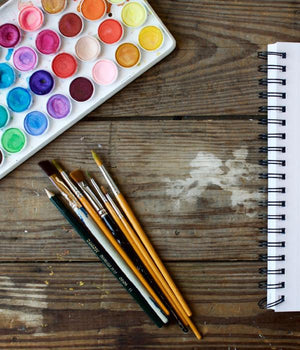Art tools, paint, brushes, pencils, and notepad