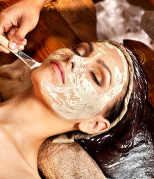 Woman receiving facial mask treatment from beauty therapist