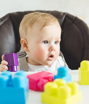 A child plays creatively with coloured blocks