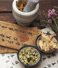 Chinese medicinal herbs, flowers, and mortar and pestle