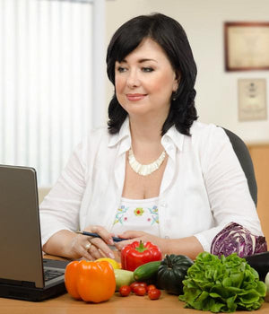 Clinical nutrition consultant at laptop computer with vegetables