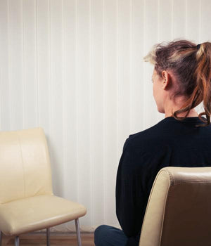 A woman sits using the Empty Chair Technique from Gestalt Therapy