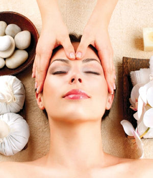Head of woman receiving beauty and wellness treatment head massage