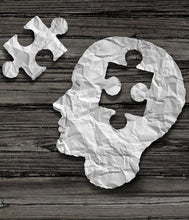 A human head and matching jigsaw piece cut from paper lay on wood