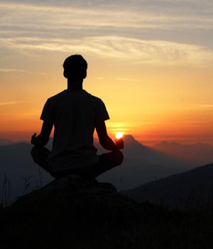 Seated man meditating on mountain at sunrise or sunset