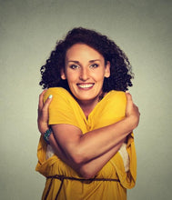 Woman wearing yellow hugs herself, smiling